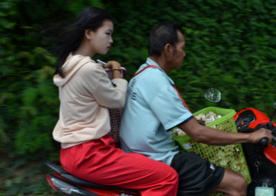 Father and daughter carrying items on a motor cycle to the market in mountains